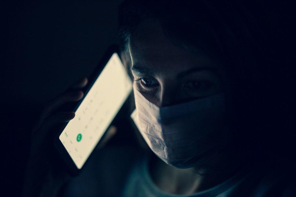 Frau mit Atemschutzmaske und Mobiltelefon